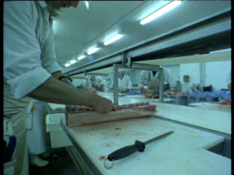 Pig parts being butchered in meat processing factory, UK