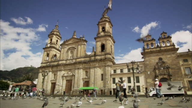 LA WS Pigeons flying as tourists walk past La Catedral Primada de Colombia in Plaza Bolivar / Bogota, Colombia