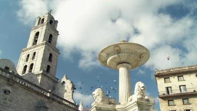ws la pigeons flying over fountain in plaza de san francisco / havana, cuba - low angle view video stock e b–roll
