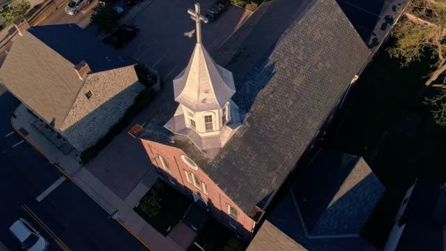 夕暮れ時にペンシルバニアの小さな町バースの教会の上を飛ぶ鳩。アメリカ合衆国ペンシルバニア州アパラチア山脈。静的カメラ、上昇運動を持つ空中ドローンビデオ。 - プロテスタント点の映像素材/bロール