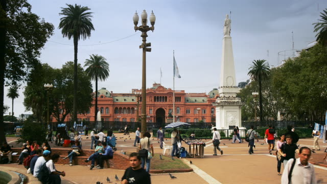 Pigeons maneuver through crowds of visitors in front of Casa Rosada and Piramide de Mayo in Buenos Aires, Argentina.