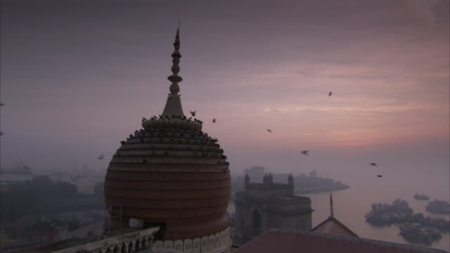 PIgeons perch on domed roof of Taj Mahal Hotel at dawn with harbour in background Mumbai. Available in HD.