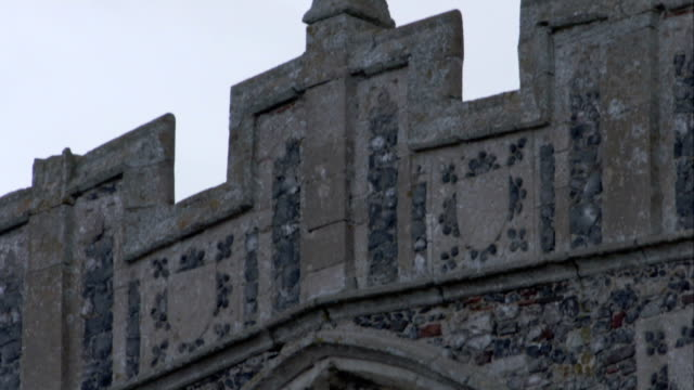 Pigeons perch on the exterior of Holy Trinity Church in Long Melford, England. Available in HD.