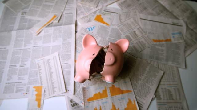 piggy bank falling and being broken over sheets of paper - hinunter bewegen stock-videos und b-roll-filmmaterial