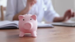 Piggy bank on table with female doctor working in background