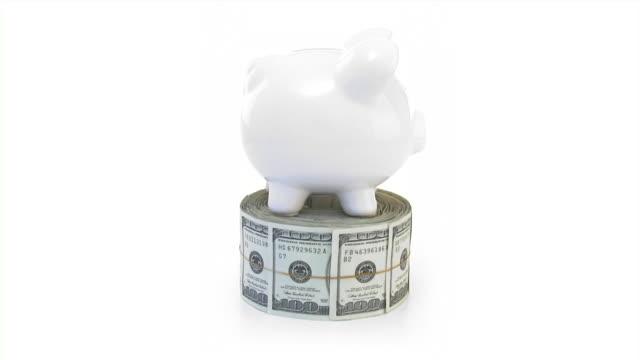 vídeos de stock, filmes e b-roll de piggy bank e pacote de moedas e dinheiro. dinheiro, conceito de finanças. - enfoque de objeto sobre a mesa