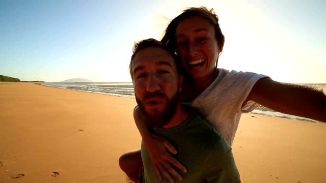 Piggyback selfie on beach