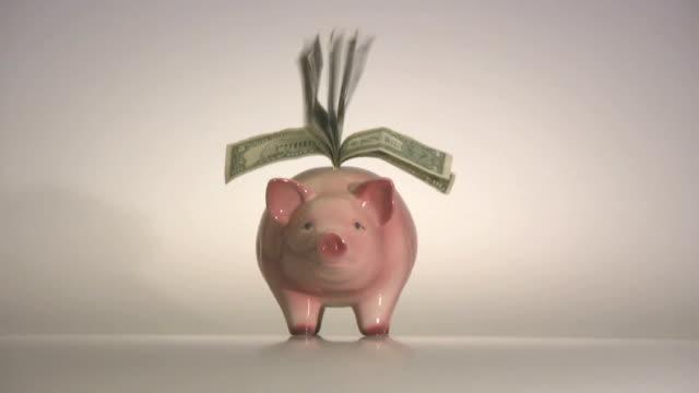 piggybank volante banconote alette - banconota da 10 dollari statunitensi video stock e b–roll
