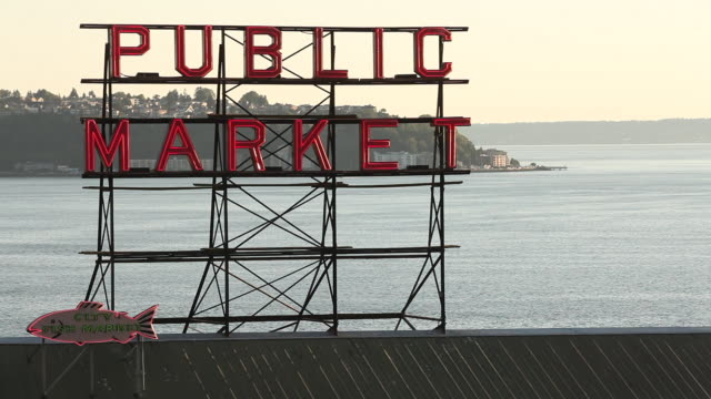 Pike Place Market sign in Seattle Washington at sunset with the Puget Sound in the background.