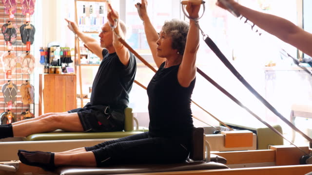 ms pilates students working out on pilates reformer during class in fitness studio - pilates stock-videos und b-roll-filmmaterial