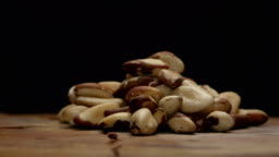 Pile of brazil nuts on a wooden table isolated on black