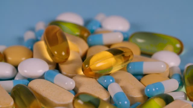 a pile of brightly-coloured pills and capsules turn on a blue background - vitamin stock videos & royalty-free footage