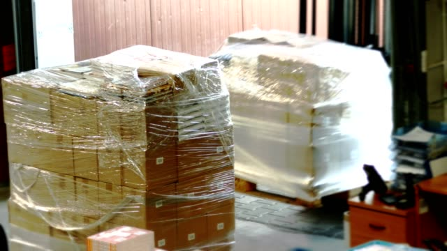 pile of cardboxes covered with foil. warehouse interior - compartment stock videos & royalty-free footage