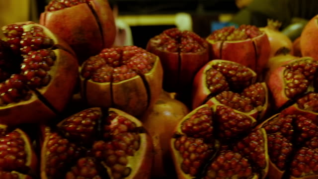 pile of cut ruby red pomegranate fruit in asia local market - torso video stock e b–roll