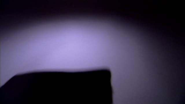 a pile of dollar bills is thrown into a spotlighted surface. - banconota da 10 dollari statunitensi video stock e b–roll