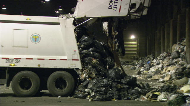 ms zi zo pile of garbage is dumped from back of truck onto ground outside of factory / new york city, new york, usa - large group of objects stock videos & royalty-free footage