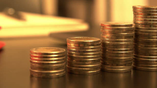 pile of golden coins on the work desk - gold colored stock videos & royalty-free footage