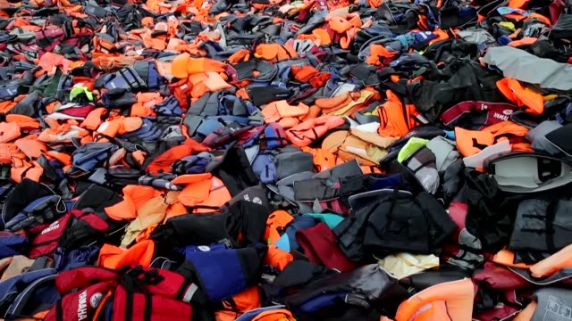 pile of lifevests and life buoys seen at a garbage dump site after refugees left in greece's lesbos island on january 20 2017 lifevests and life... - flytväst bildbanksvideor och videomaterial från bakom kulisserna