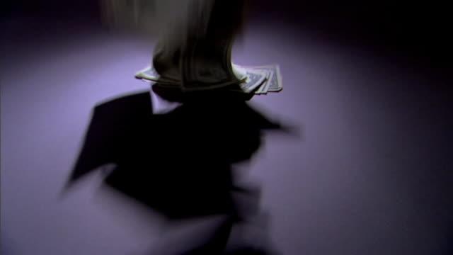 a pile of money falls onto a spotlighted surface. - banconota da 10 dollari statunitensi video stock e b–roll