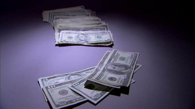 a pile of money is thrown onto a spotlighted surface. - banconota da 10 dollari statunitensi video stock e b–roll