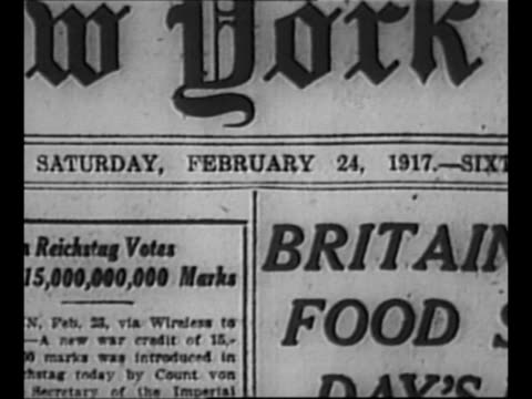 pile of newspaper front pages; to new york times front page dated 1917 / pile of newspaper stories; zoom into headline about food riots / crowd of... - newspaper headline stock videos & royalty-free footage