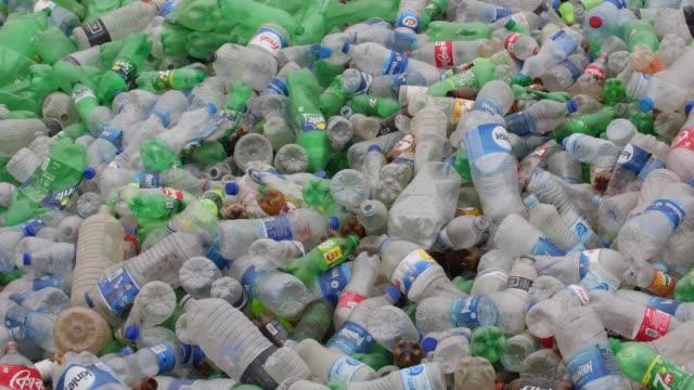 vídeos de stock e filmes b-roll de pile of plastic bottle seen in garbage dump site area in dhaka, bangladesh on december 21. - depósito de lixo
