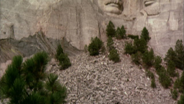 A pile of rocks rest under Mount Rushmore.