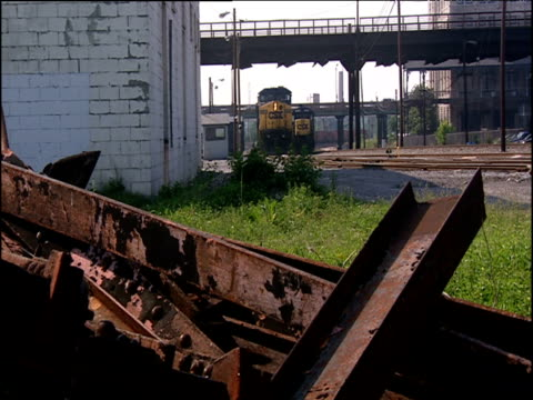 pile of rusty girders in foreground freight trains in background man climbs into cab of train - imperfection stock videos & royalty-free footage