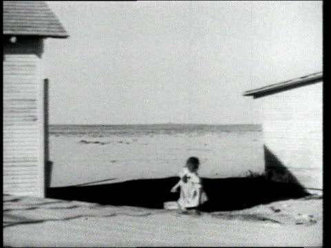 vídeos y material grabado en eventos de stock de pile of sand on farm / girl carrying bucket through sand past farmhouse - usa