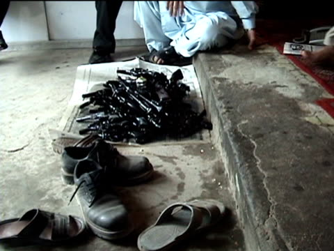 stockvideo's en b-roll-footage met ms pile of shoes and guns at entrance of gun shop darrah in swat agency of tribal zones federally administered tribal areas pakistan audio - vuurwapenwinkel