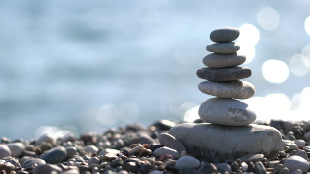 pile of stones at the beach - buddhism stock videos & royalty-free footage