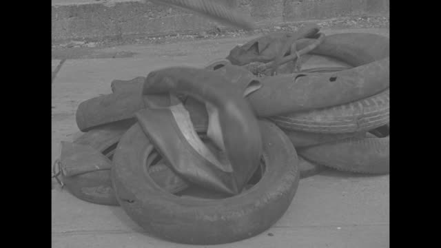 pile of used tires on sidewalk, with other rubber items being thrown into shot from off-camera / vs drive-by shots outdoor lot full of used tires,... - reifenschlauch stock-videos und b-roll-filmmaterial