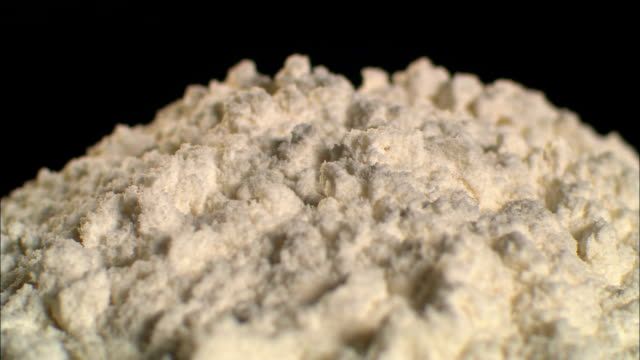 a pile of white flour rotates against a black background. - flour stock videos & royalty-free footage