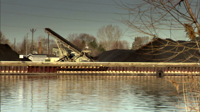 piles of black coal & coal elevator on bank of fox river, calm waters & bare tree fg. import, export, cargo, goods, commodity, freight, terminal. - freight elevator stock videos & royalty-free footage