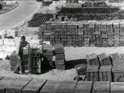 stockvideo's en b-roll-footage met b/w 1956 piles of boxes of ammunition / man opens one box / middle east / suez crisis / newsreel - suezcrisis
