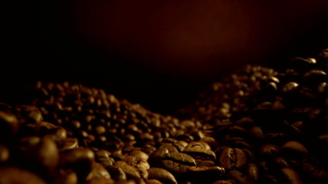 piles of coffee beans laying around and camera is hovering above with yellow black background a macro shot on red epic and laowa - grinding stock videos & royalty-free footage