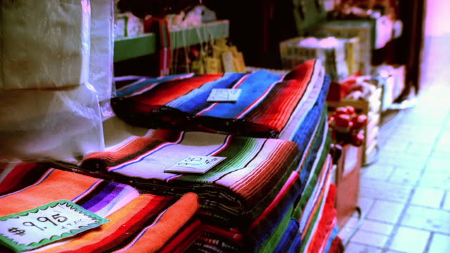 vidéos et rushes de zi piles of folded mexican blankets on a vendor's table in the olvera street marketplace, with overly brilliant colors / los angeles, california, united states - procédé croisé