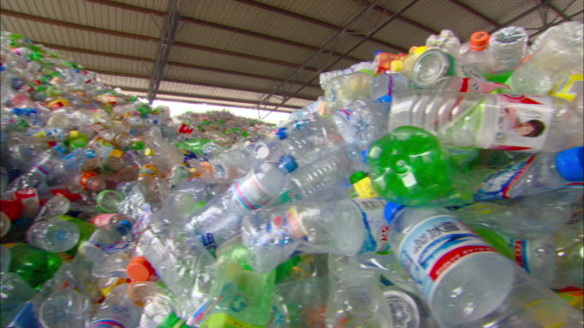 ms pan piles of loose plastic bottles in recycling center, beijing, beijing, china - bottiglia video stock e b–roll