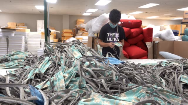 piles of masks surround a worker at northcape, an outdoor furniture manufacturer, as he makes personal protective equipment during the coronavirus... - protective workwear stock videos & royalty-free footage