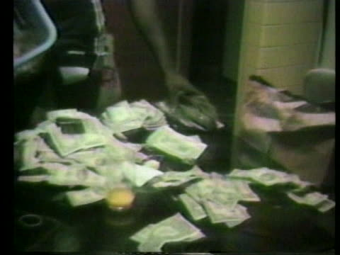 piles of money cover a table as a hand rifles through a stack of bills - hamper stock videos & royalty-free footage
