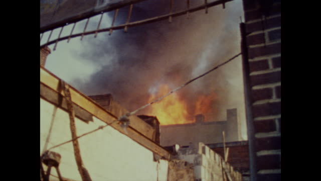 stockvideo's en b-roll-footage met piles of red brick smolder in front of a backdrop of burned out buildings destroyed stores and barely standing structures - demonstrant