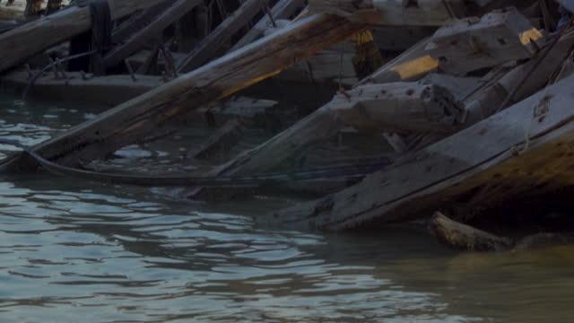 piles of rubble and broken boats on al muharraq coast - rubble stock-videos und b-roll-filmmaterial