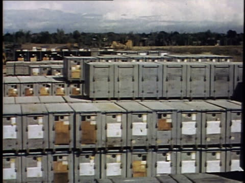 piles of tires and other military stores / stacks of crates / piles of munitions / trucks driving / aircraft on flightline - グアム点の映像素材/bロール
