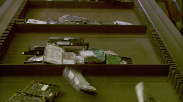 ms la td pan piles of used hard drives on conveyor belt moving upwards, birmingham, uk - エレクトロニクス産業点の映像素材/bロール