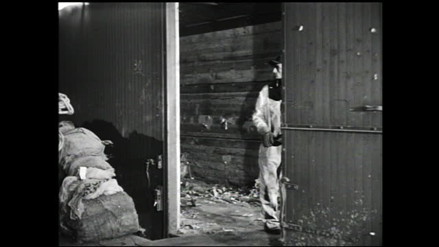 piles of wires; skinny moulds being filled; hand holding a slate over burning furnace, worker tending to the furnace, poking it with a stick; worker... - 1940 1949 bildbanksvideor och videomaterial från bakom kulisserna