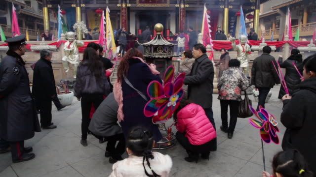 ms tu pilgrim burning incense to pray for good luck and wealth at god of wealth temple during chinese spring festival / xi'an, shaanxi, china - chinesisches laternenfest stock-videos und b-roll-filmmaterial