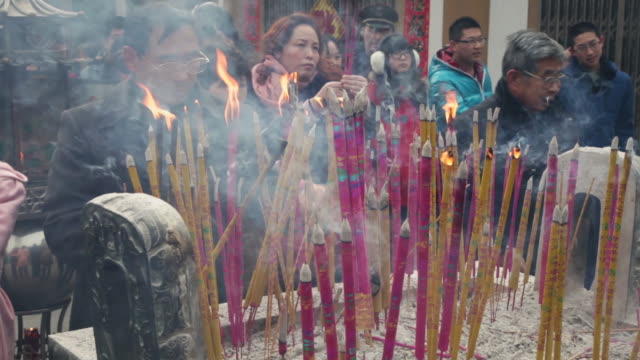 ms pilgrim burning incense to pray for good luck and wealth at god of wealth temple during chinese spring festival / xi'an, shaanxi, china - pilgrim stock videos & royalty-free footage