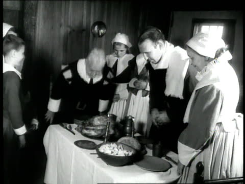 a pilgrim family stands around a dinner table and prays during a 1660s era reenactment - pellegrino video stock e b–roll