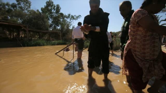 pilgrims and baptists at qasr el yahud baptism site in the jordan river valley, israel - baptist bildbanksvideor och videomaterial från bakom kulisserna