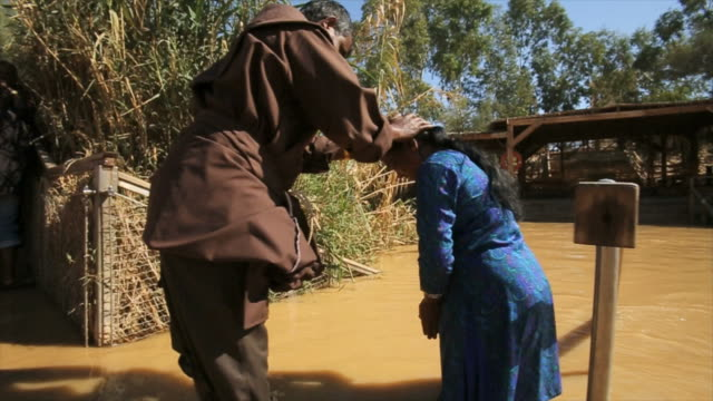 pilgrims and baptists at qasr el yahud baptism site in the jordan river valley, israel - バプテスト点の映像素材/bロール